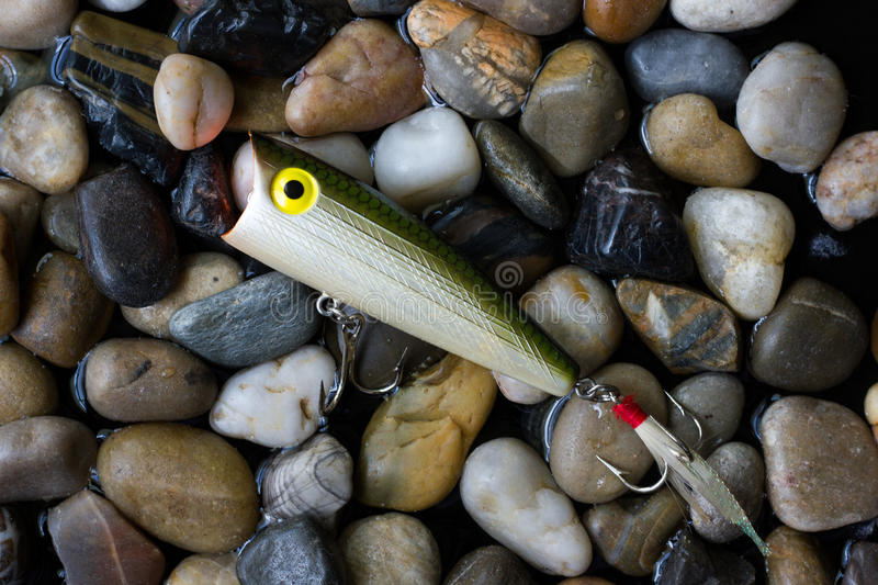 Bass Lure. A bass popper lure resting on pebbles royalty free stock photo