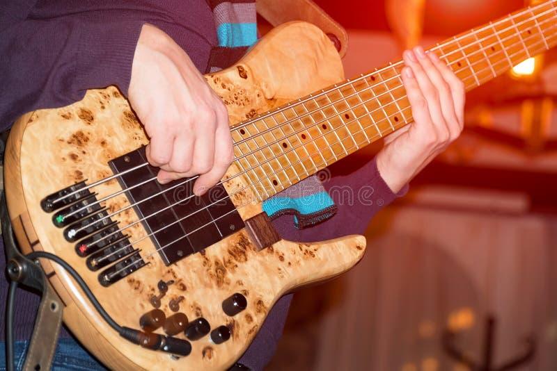 The bass player plays a five-string bass guitar close-up stock photos