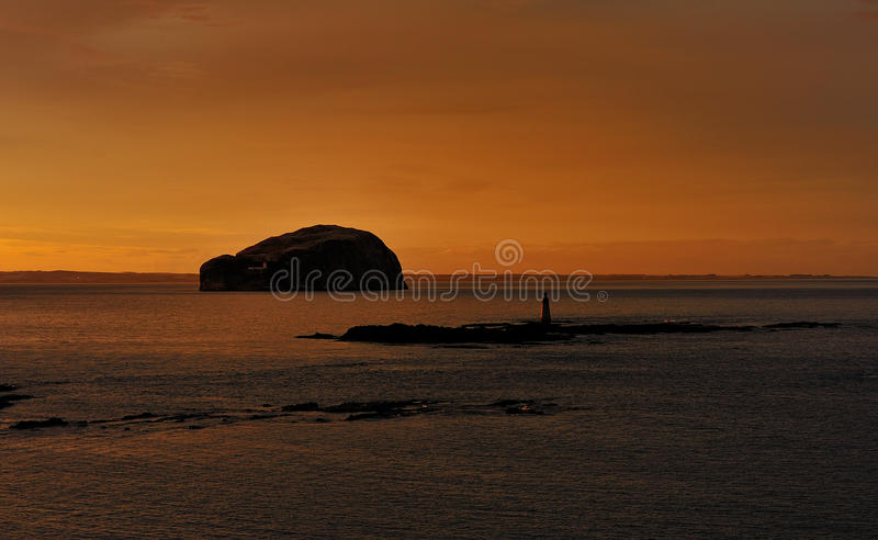 Bass rock, firth of forth. A view of the famous Bass rock at sunset, in the firth of forth, Scotland. Taken from the shore at east Berwick, to show the rocks at royalty free stock image