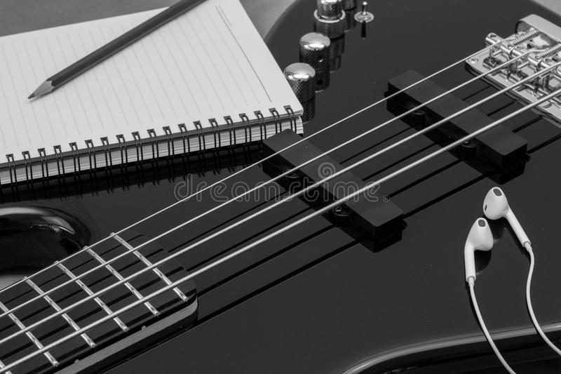 Bass Song Writing. Close up shot of an electric bass, pen and ear phones symbolizing creativity while writing a song royalty free stock photography