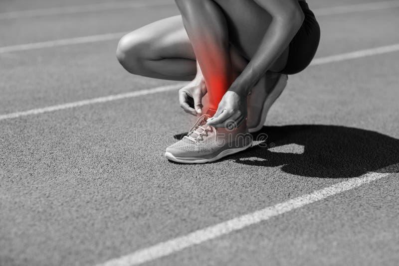 Basse section d'athlète attachant la dentelle sur la voie de sports images stock