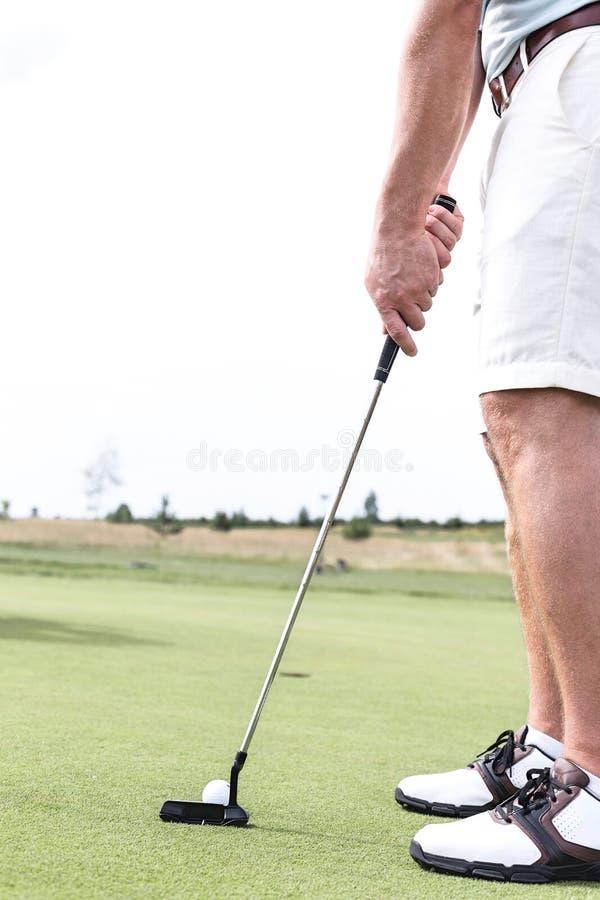 Basse section d'homme de mi-adulte jouant le golf contre le ciel clair images libres de droits