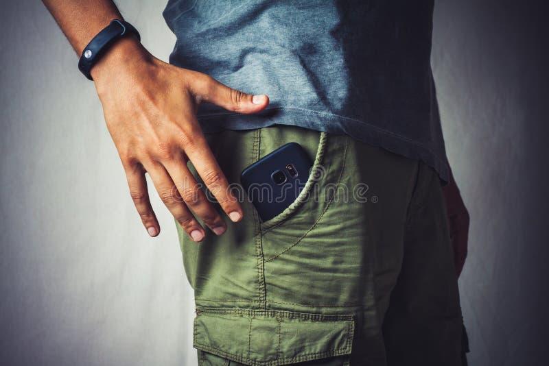 Basse section d'un homme à l'aide du smartphone photo stock