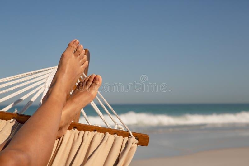 Basse section de femme détendant sur l'hamac à la plage image stock