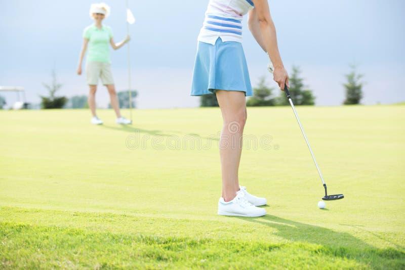 Basse section de femme jouant le golf avec l'ami féminin photographie stock libre de droits