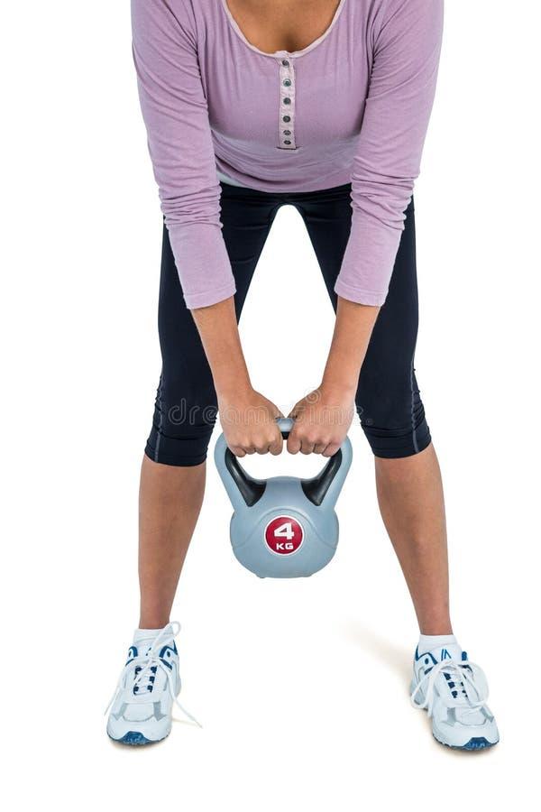 Basse section de femme s'exerçant avec le kettlebell photo stock