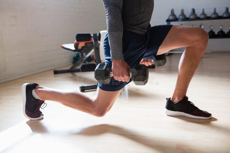Basse section de l'athlète masculin exerçant des mouvements brusques dans le club photo stock