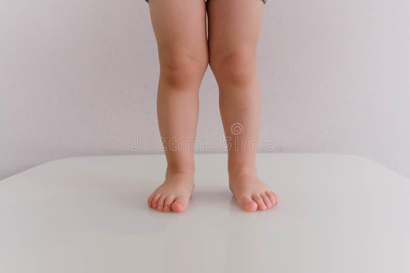 Basse section de la position de bébé garçon les pieds plats de 2 années dans un enfant, les jambes tombent vers le bas photographie stock