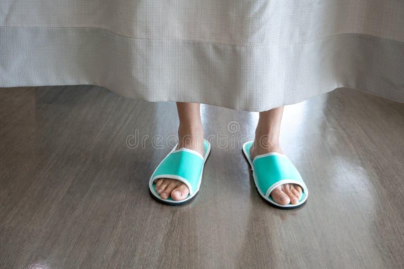 Basse section de plan rapproché des pieds du ` un s de personne portant le beh vert de pantoufle image stock