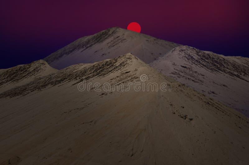 Bassi rossi del sole dietro la montagna della sabbia fotografia stock libera da diritti