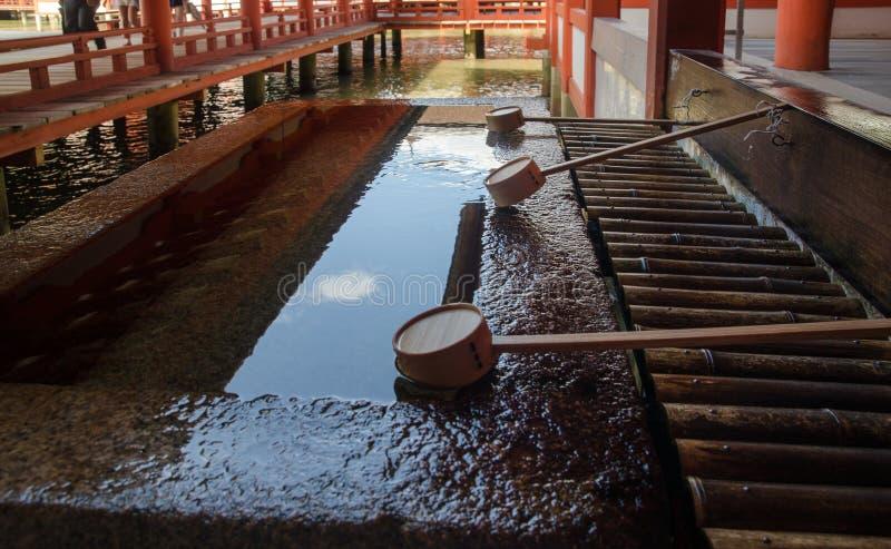 bassin voor geestelijke reiniging in Itsukushima-Heiligdom Is een Shinto-heiligdom op het eiland van Itsukushima-aka Miyajima stock foto's