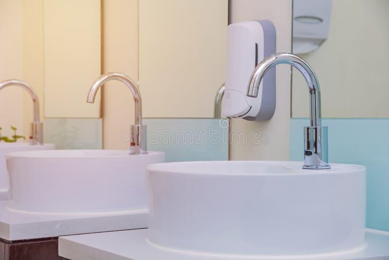 bassins blancs dans l'intérieur de salle de bains avec les tuiles granitiques image libre de droits