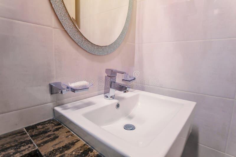 bassins blancs dans l'intérieur de salle de bains avec les tuiles granitiques photo libre de droits