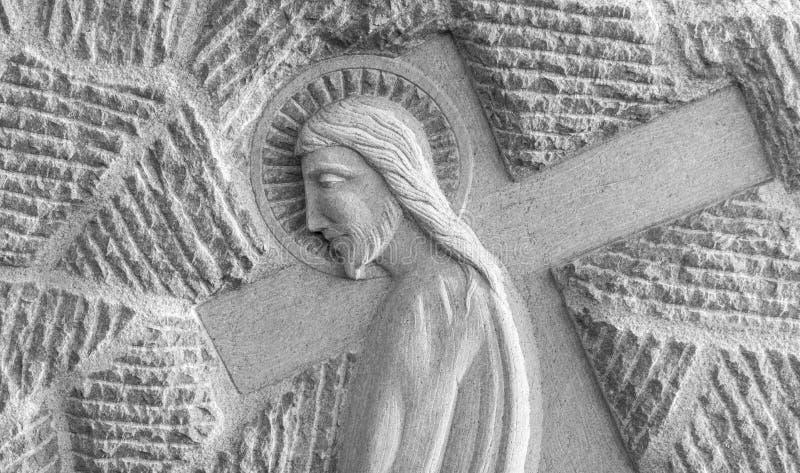 Bassorilievo di Gesù che porta il suo incrocio fotografia stock libera da diritti