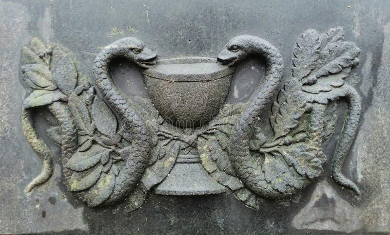 bassorilievo sotto forma di due serpenti e di ciotola sulla superficie immagine stock libera da diritti