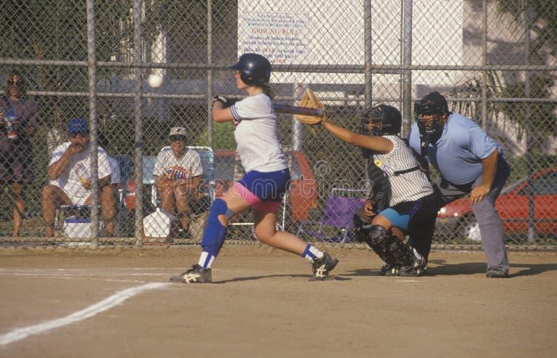 Bastão de balanço da menina no jogo do softball das meninas imagens de stock