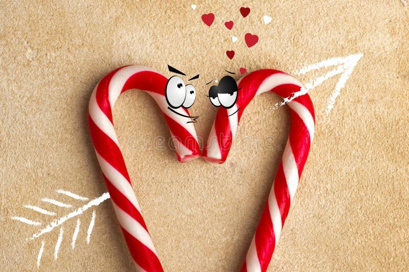 Bastão de doces com um símbolo da seta, coração perfurado de dois amantes fotografia de stock