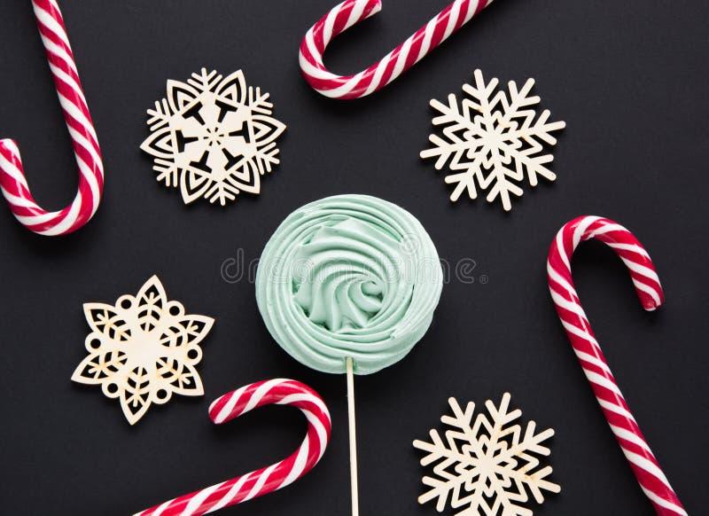 Bastão de doces do Natal, marshmallow da hortelã, floco de neve branco no fundo preto Fundo do Natal imagem de stock royalty free