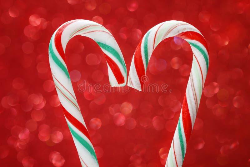 Bastón de caramelo de la Navidad en fondo rojo foto de archivo libre de regalías