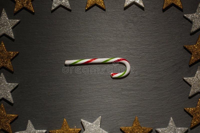 Bastón de caramelo rayado en fondo negro de la pizarra imagen de archivo