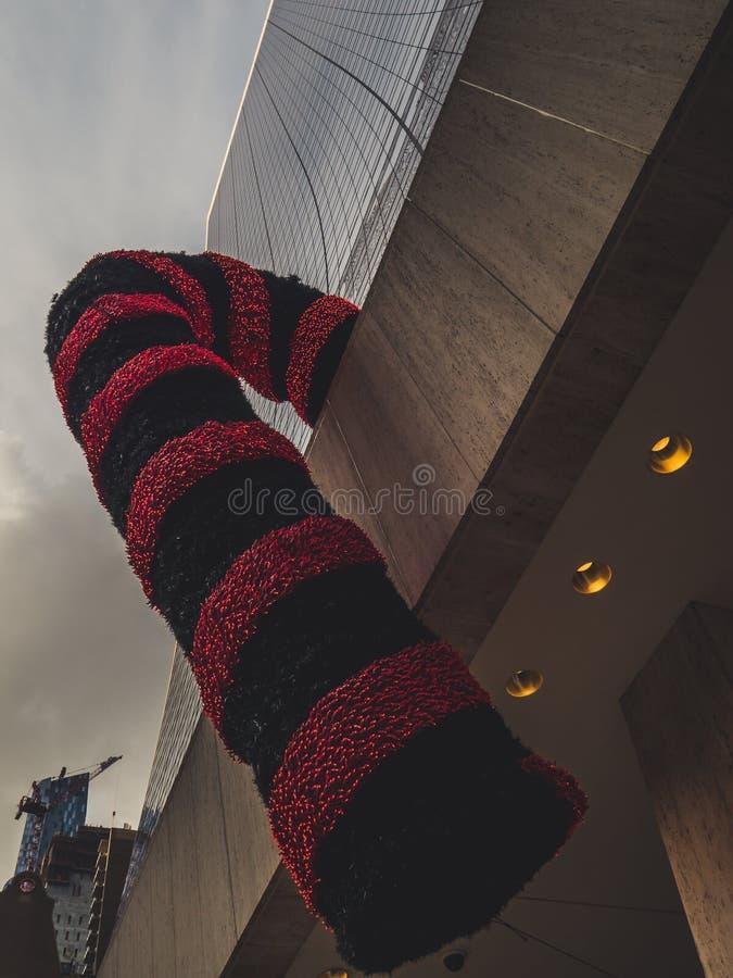 Bastón de caramelo real gigante de la Navidad que cuelga abajo de una decoración de la Navidad del edificio imagen de archivo