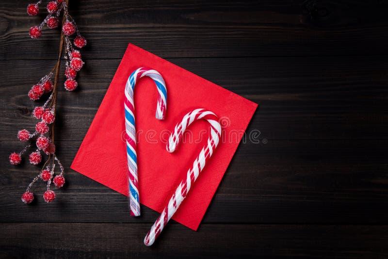 Bastões de doces do Natal no guardanapo vermelho com as bagas vermelhas congeladas na tabela de madeira escura Fundo do Natal ou  foto de stock royalty free