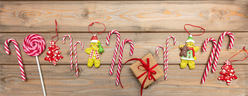 Bastões de doces, ornamento do Natal e uma caixa de presente com a fita vermelha no fundo de madeira, bandeira, vista superior fotografia de stock royalty free