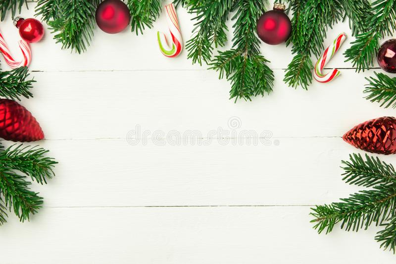 Bastões de doces vermelhos macios frescos das bolas do ornamento dos ramos de árvore do abeto no contexto de madeira da prancha b fotos de stock royalty free
