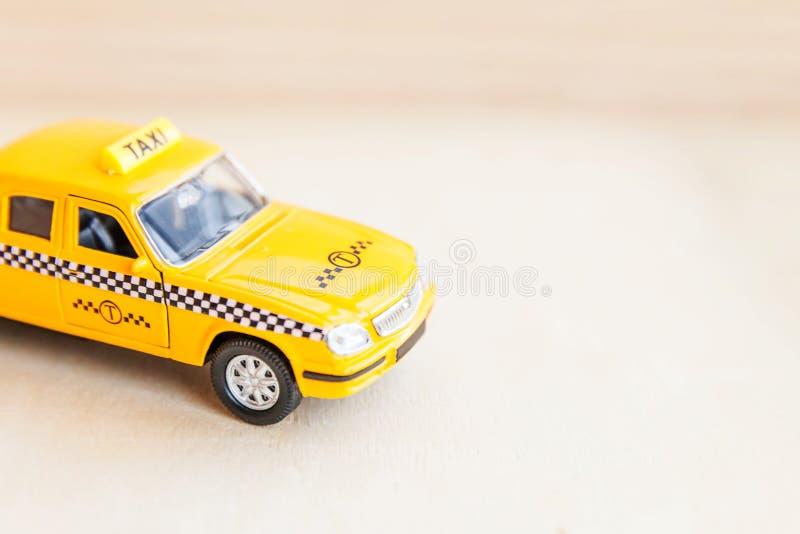 Basta projetar modelo de táxi táxi táxi para retrô-toy de cor amarela em fundo de madeira Símbolo do automóvel e do transporte Tr foto de stock royalty free