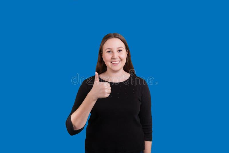 Bastante donante de la señora pulgares encima de la sonrisa dulce en fondo azul imágenes de archivo libres de regalías