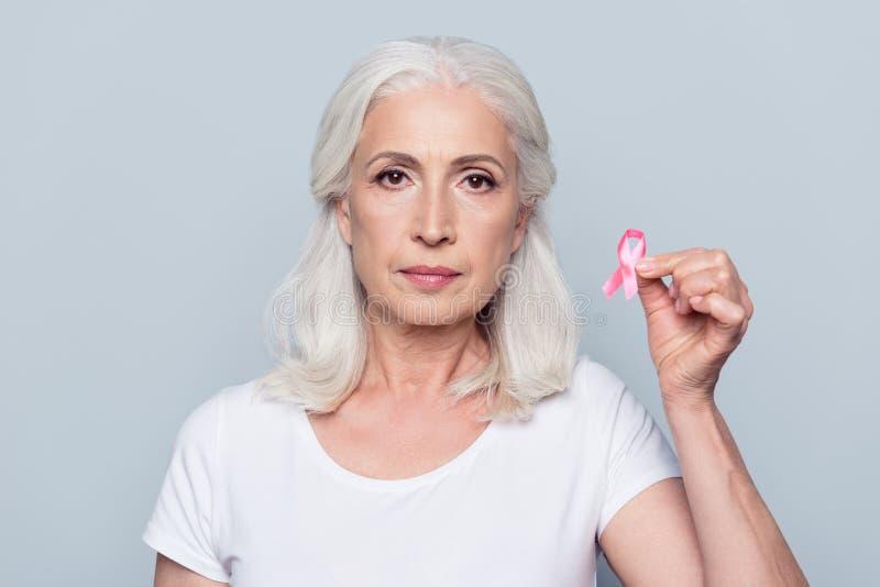 Bastante, mujer atractiva, envejecida, voluntaria que sostiene el pecho rosado Ca fotos de archivo libres de regalías