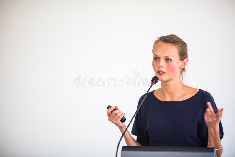 Bastante, mujer de negocios joven que da una presentación en una conferencia/que hace frente al ajuste imagen de archivo libre de regalías