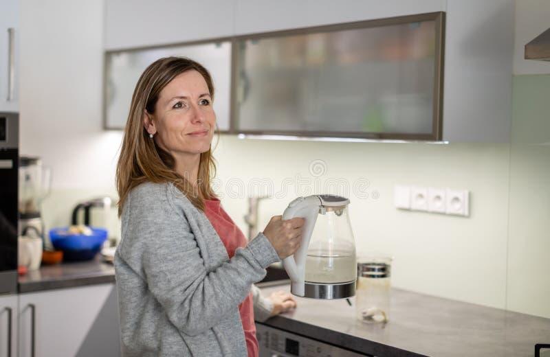 Bastante, mujer joven en su cocina brillante moderna imagen de archivo