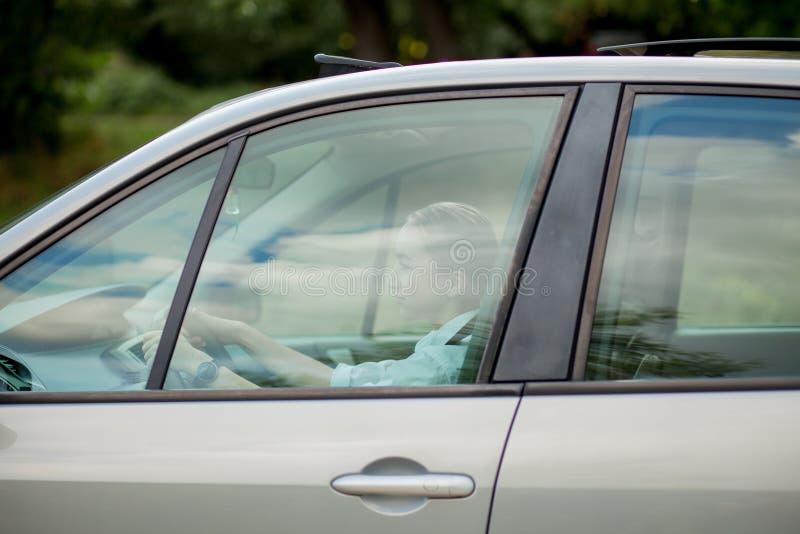 Bastante, mujer joven que conduce una invitaci?n automotriz a viajar Alquiler de coches o vacaciones foto de archivo