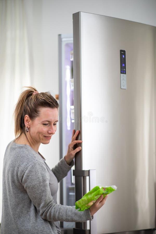 Bastante, mujer joven que saca los ultramarinos del refrigerador, comprobando las fechas foto de archivo libre de regalías