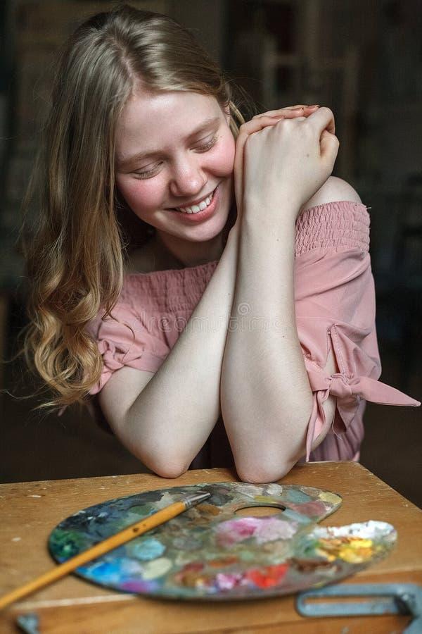 Bastante rubio joven en vestido rosado con el pelo ondulado lleva a cabo las manos juntas y las risas delante de la paleta en est imagen de archivo libre de regalías