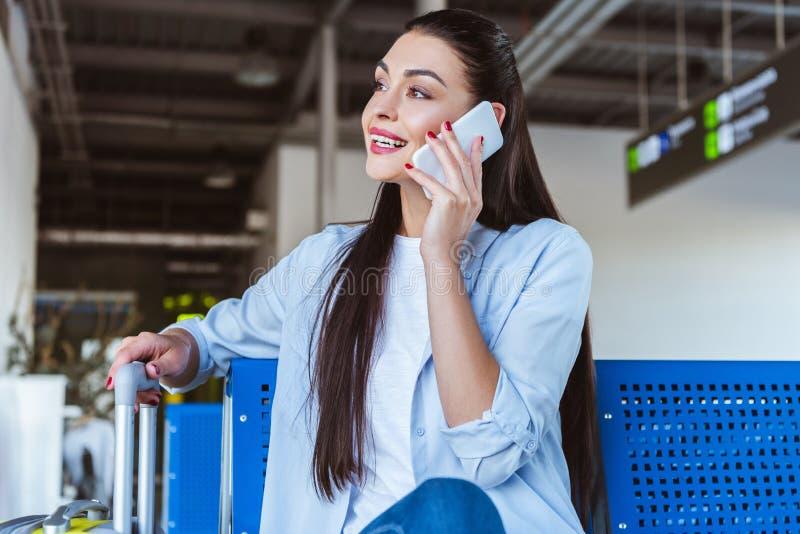 Bastante señora que habla en un smartphone mientras que se sienta foto de archivo