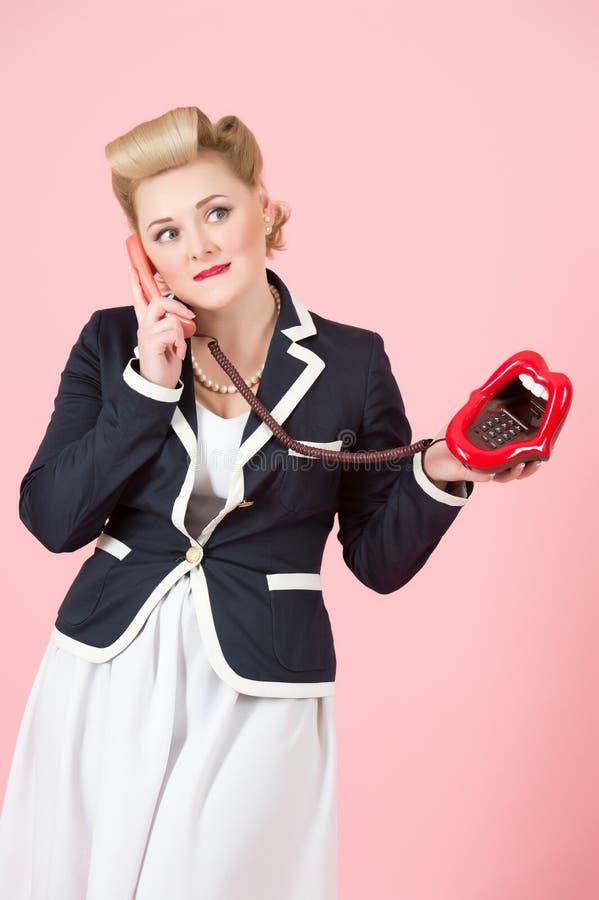 Bastante señora que parece interesada mientras que teniendo charla del teléfono imagen de archivo