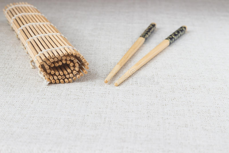 Bastoncini dei sushi con la stuoia di bambù rotolata della paglia immagini stock