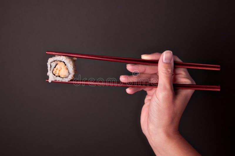 Bastoncini destri della tenuta e un pezzo di sushi immagini stock