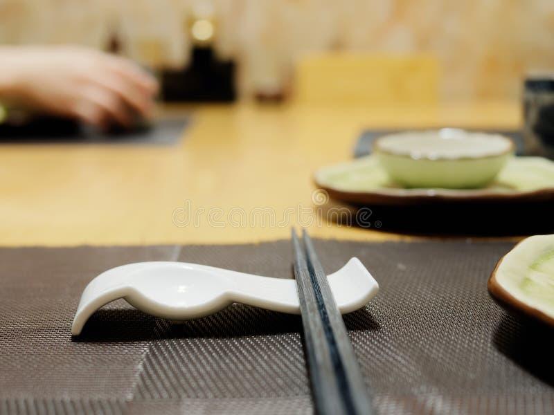 Bastoncini di bambù di legno sulla tavola con le ciotole ed il fondo femminile della mano Concetto del menu o del pasto orientale fotografia stock
