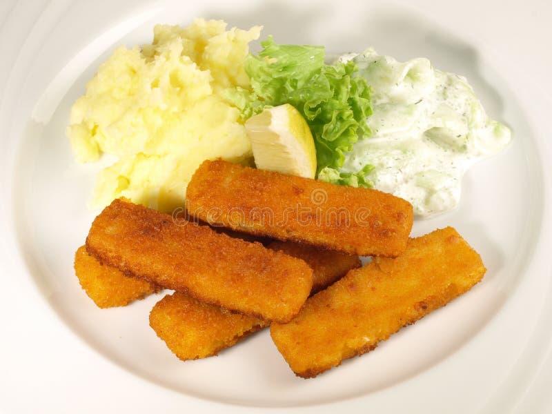 Bastoncini di pesce con la patata fracassata fotografia stock