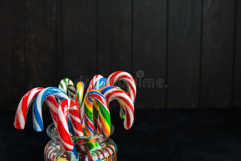 Bastoncini di zucchero variopinti di natale in barattolo di vetro su fondo di legno fotografie stock
