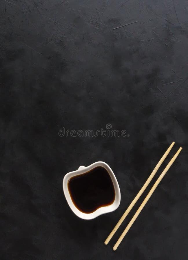 Bastoncini e salsa di soia su fondo nero immagine stock libera da diritti
