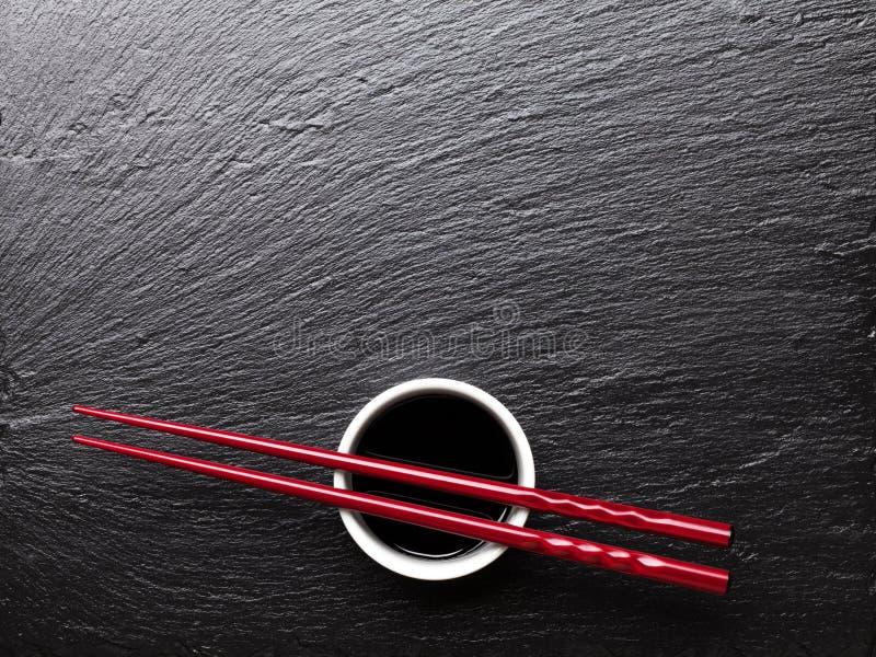 Bastoncini giapponesi dei sushi sopra la ciotola della salsa di soia immagine stock