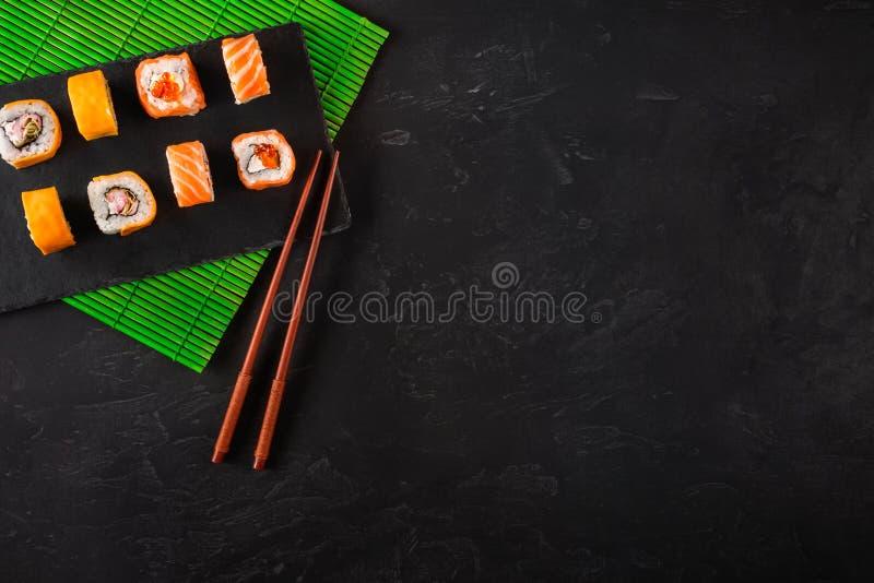 Bastoncini giapponesi dei sushi sopra la ciotola della salsa di soia, riso su fondo di pietra nero Vista superiore con lo spazio  fotografie stock libere da diritti