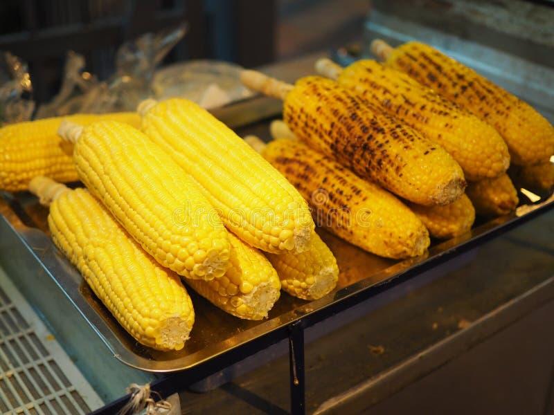 Bastone bollito e grigliato del cereale accatastato sulla maglia, mercato di notte fotografia stock