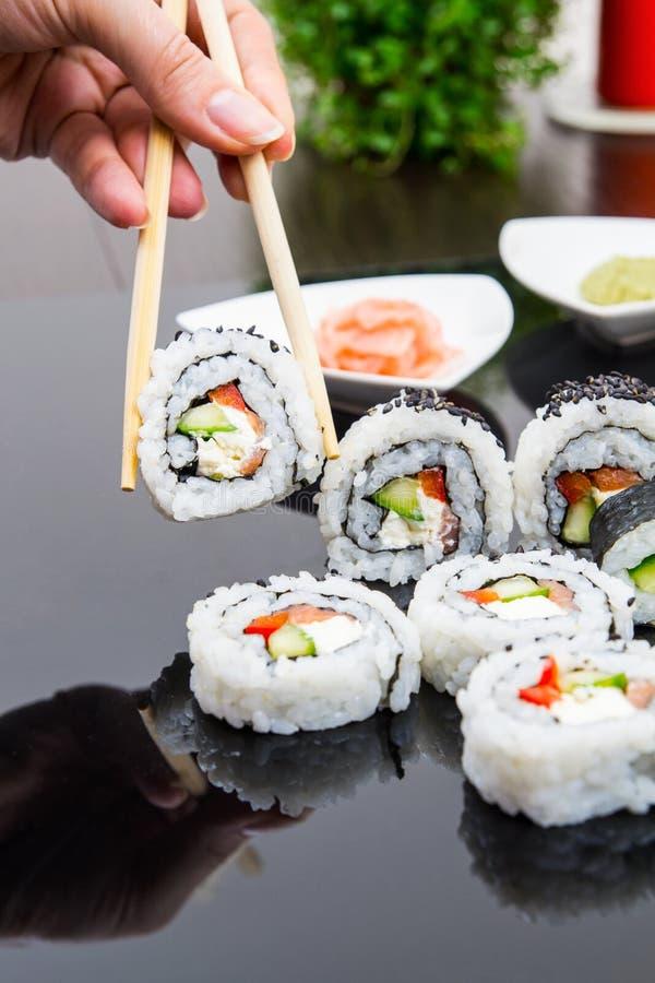 Bastone Della Tenuta Della Mano Con L Insieme Dei Sushi Di Maki Fotografie Stock Libere da Diritti
