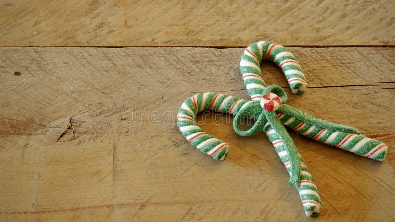 Bastones de caramelo atados en un arco en un fondo de madera imágenes de archivo libres de regalías