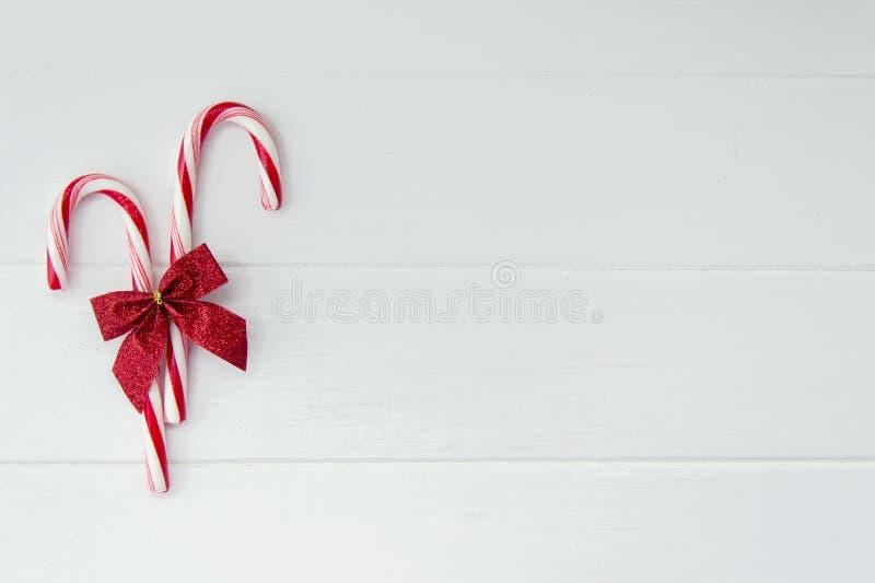 Bastones de caramelo en el fondo de madera blanco foto de archivo